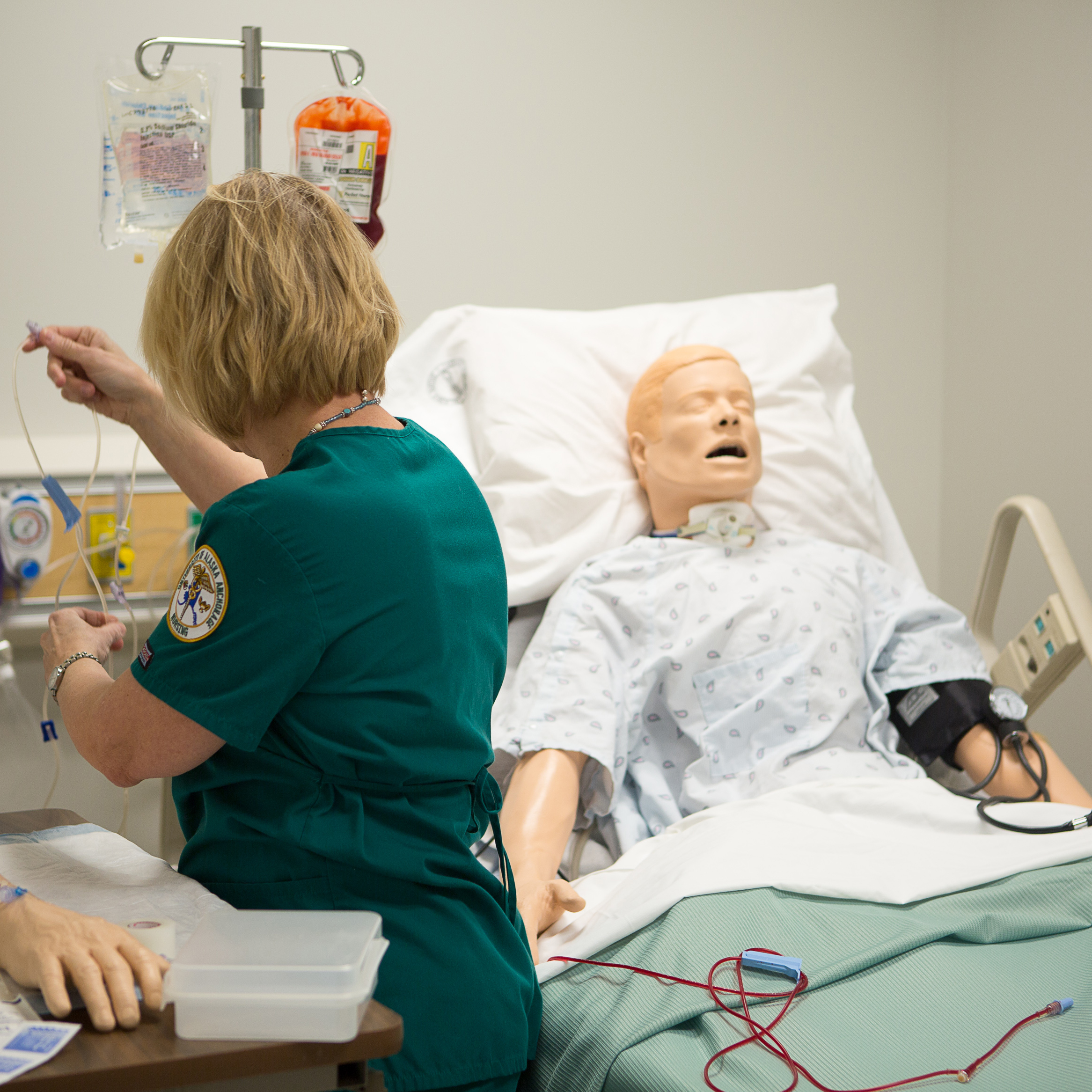 Woman checking saline bag for Sim patient.