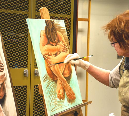 student at easel in art studio