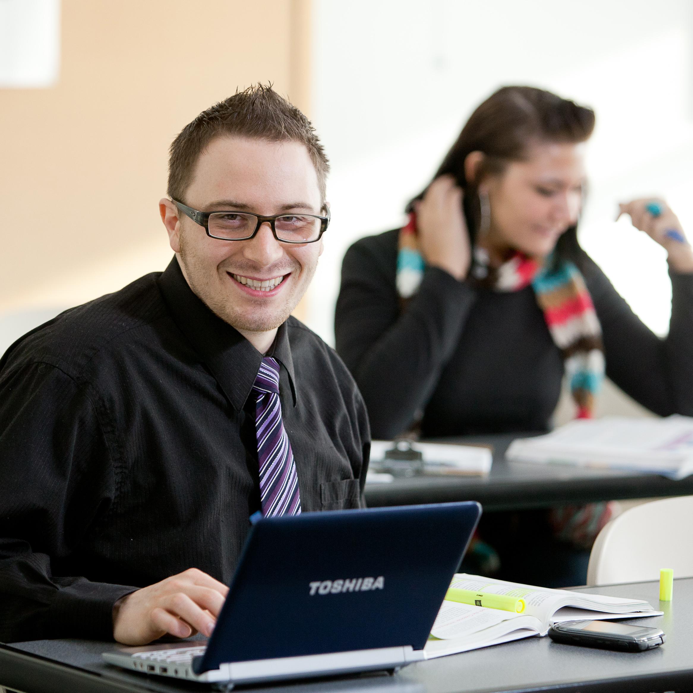 Man in tie typing on keyboard.