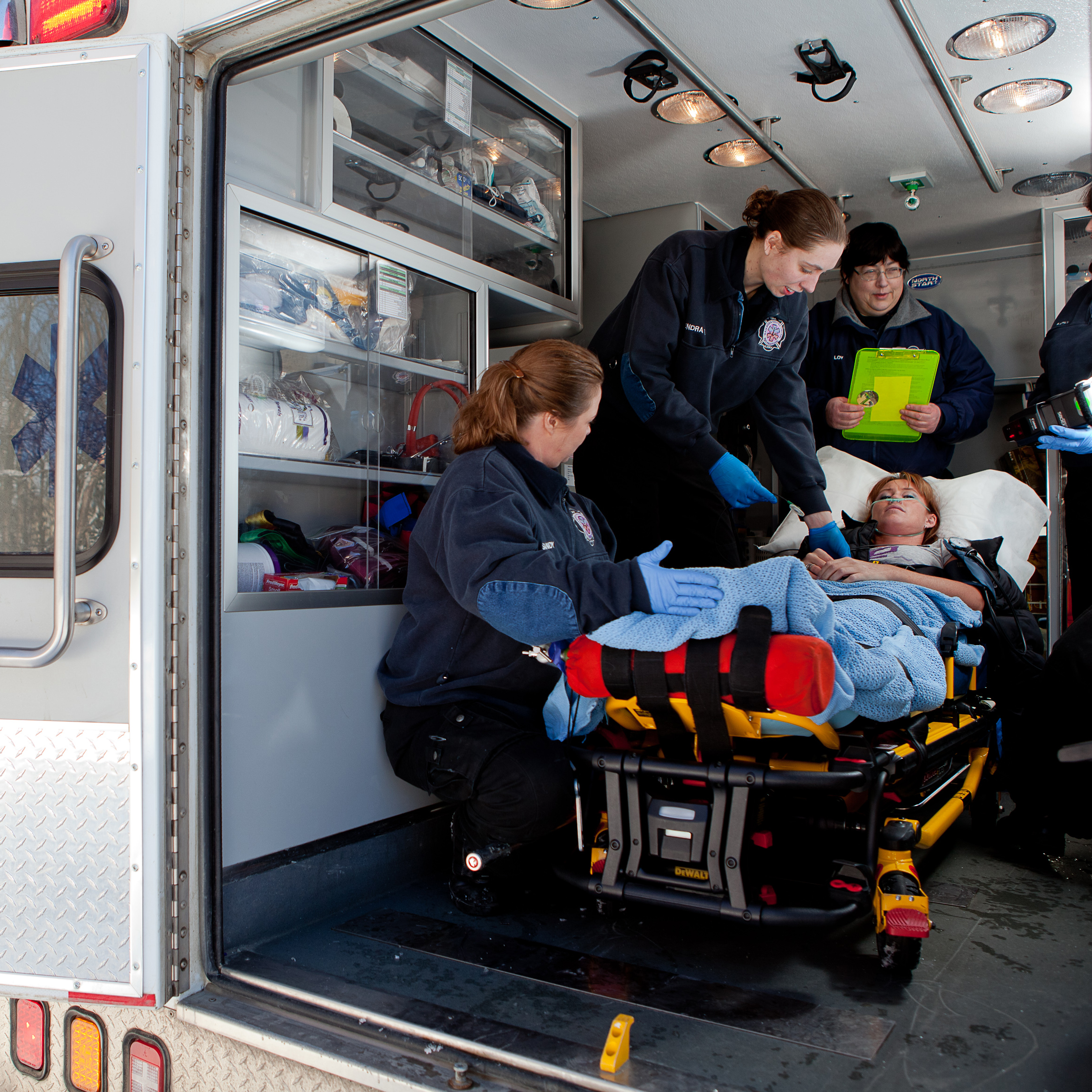 Four paramedics attending to a woman in a stretcher in the back of an ambulence.