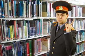 A uniformed officer with finger raised as a warning stands in front of library books.
