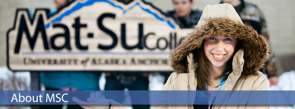 college student in a winter parka with hood pulled up and smiling in front of Mat-Su College sign in the snow