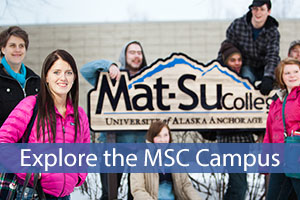 Visit Mat-Su College with a group of students gathered around the sign outside.